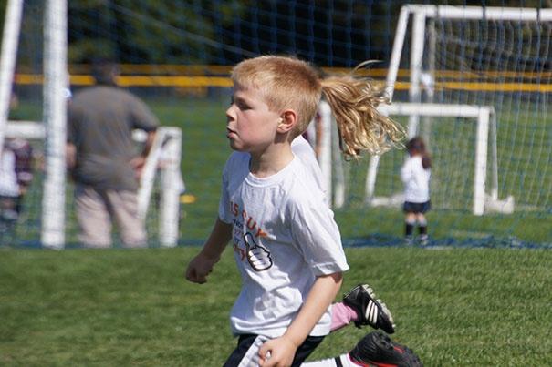 мальчик играет в футбол, хвост на голове