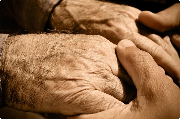 сын держит за руку старика