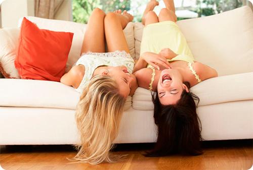 две девушки на диване смеются