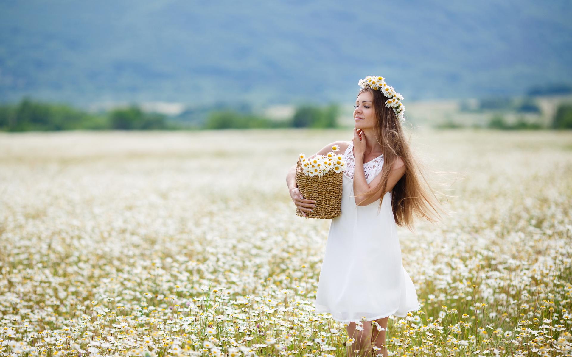 девушка на поле с венком на голове из ромашек