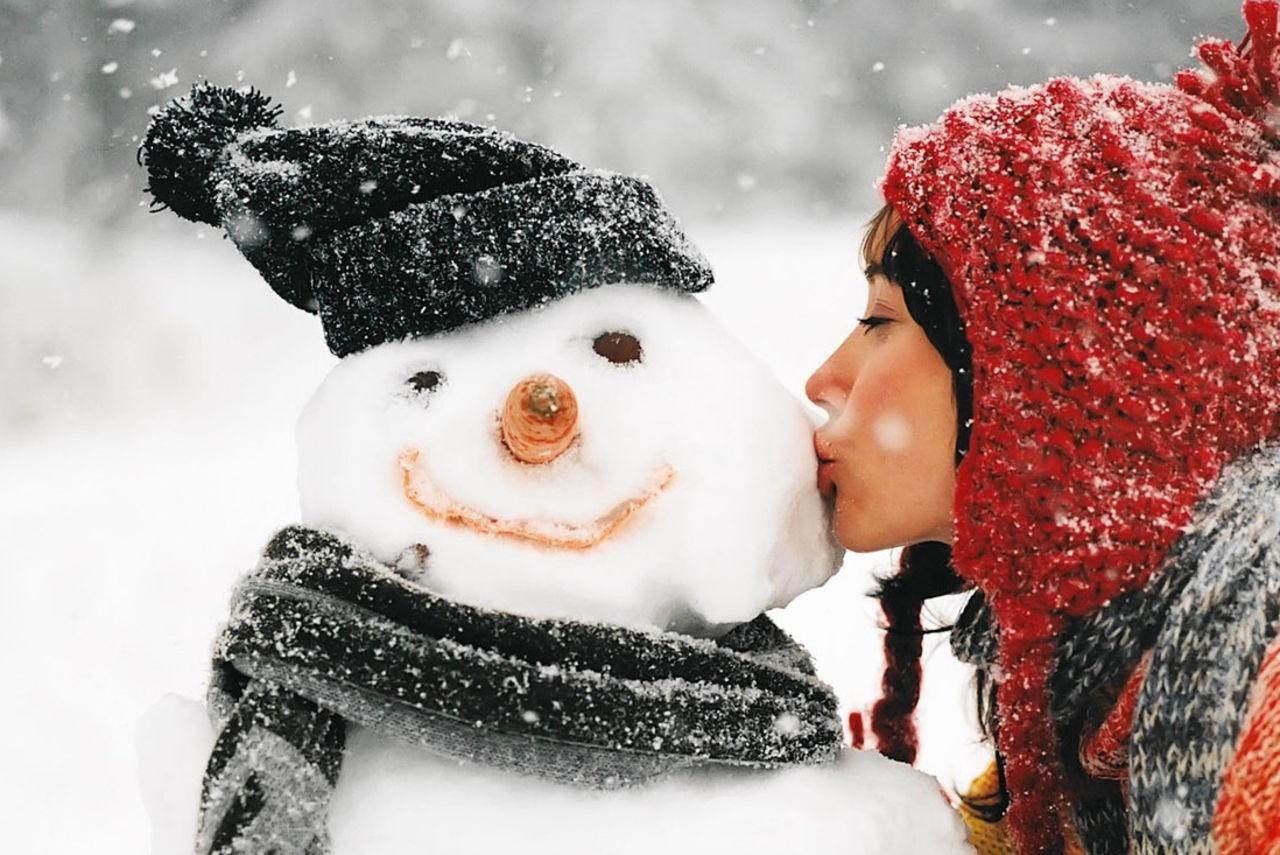 девушка целует снеговика