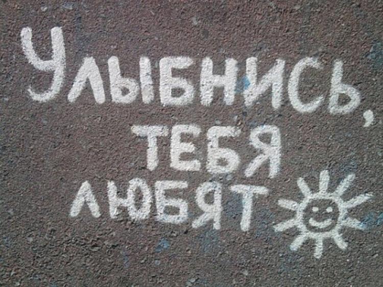надпись на асфальте: улыбнись, тебя любят