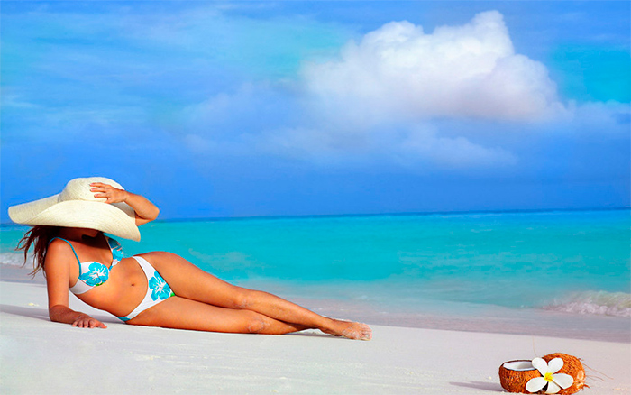 модель лежит на песке в шляпе