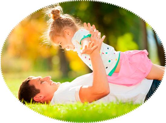 папа играет с дочкой на траве