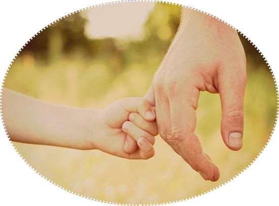 ребенок держит взрослую руку за палец