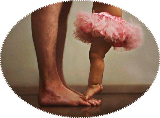 малышка стоит на папиных ножках