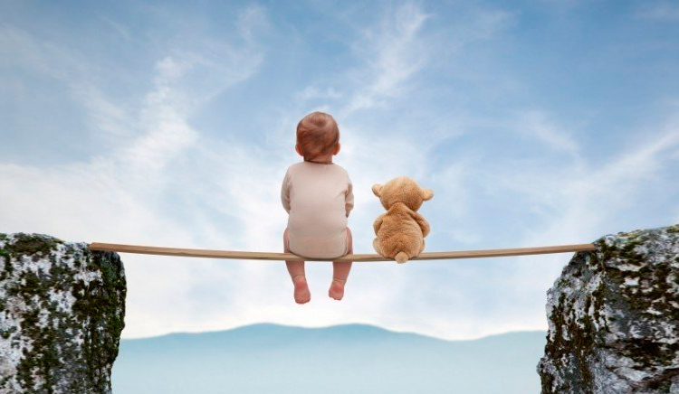 мальчик с мишкой сидит на веревке