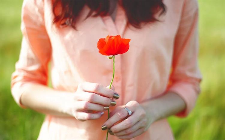 женщина держит в руке цветок мака